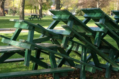 Green benches stacked together in the park.